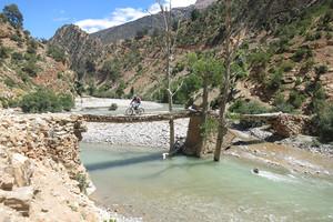 Mountainbiker überquert Fluss in Marokko
