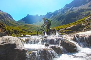 mountainbiker_durchquert_bach_bei_transalp_zum_pfundererjoch